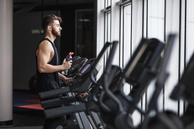Retrato de jovem desportista fazendo exercícios aeróbicos e bebendo água no ginásio