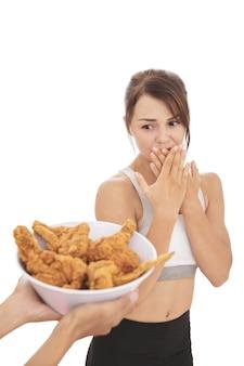 Retrato de jovem desportiva resistindo à tentação do frango frito