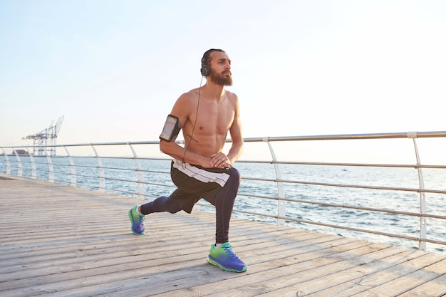 Retrato de jovem desportivo barbudo fazendo alongamento, exercícios matinais à beira-mar, ouvindo músicas legais em fones de ouvido.