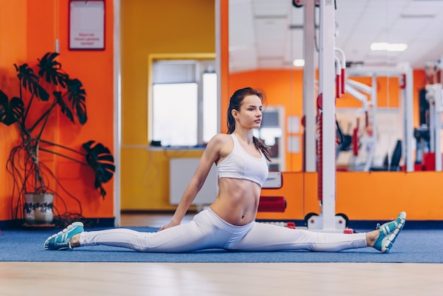 Retrato de jovem desportivo fazendo alongamento no ginásio