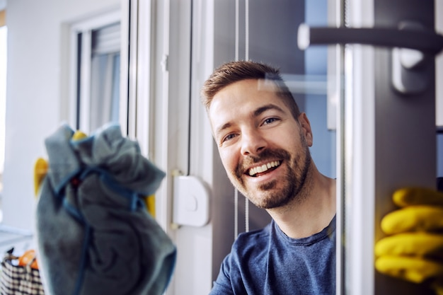 Retrato de jovem digno sorridente barbudo com luvas de borracha na janela de limpeza em casa.