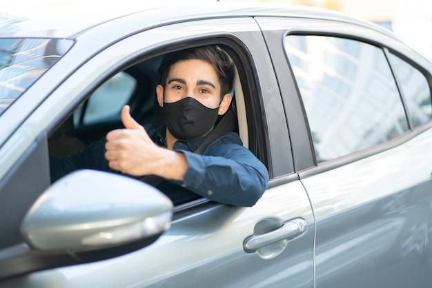 Retrato de jovem dirigindo o carro dele e mostrando o polegar. novo conceito de estilo de vida normal.