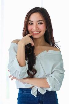 Retrato de jovem e bonita garota asiática posar para a câmera com cara feliz auto-confiante e amigável.