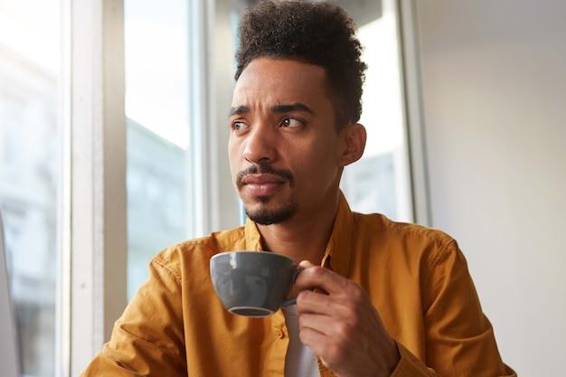 Retrato de jovem e bonito barista de pele escura, duvidoso, bebe café aromático de uma câmera cinza e desvia o olhar pensativamente, tentando provar o gosto do grão.