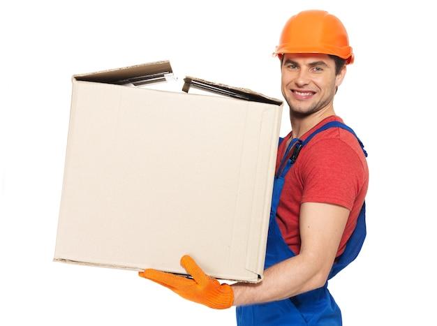 Retrato de jovem e bonito entregador com caixas de papel isoladas na parede branca