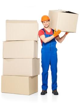 Retrato de jovem e bonito entregador com caixas de papel isoladas no fundo branco