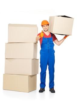 Retrato de jovem e bonito entregador com caixas de papel mostrando o sinal de positivo isolado no branco