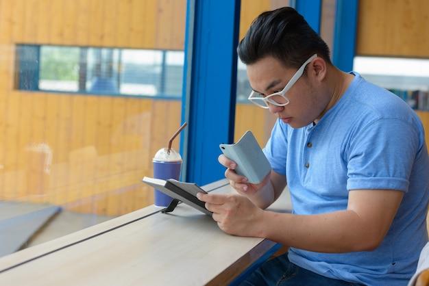 Retrato de jovem e bonito filipino com excesso de peso relaxando em uma cafeteria