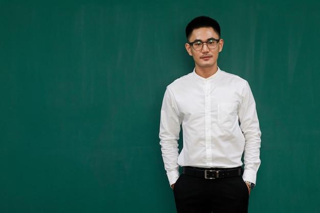 Retrato de jovem e bonito homem asiático, usando óculos e roupas de negócios casuais, camisa branca e calça preta, pose de autoconfiança com fundo verde e espaço de cópia em pé.