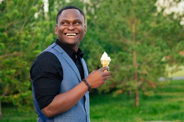 Retrato de jovem e bonito modelo elegante, homem afro-americano em um elegante terno azul em um parque de verão inteligente latino hispânico empresário negro comendo sorvete em um chifre de waffle.