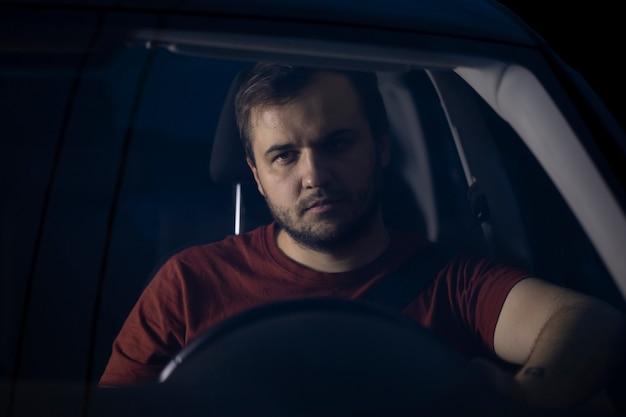 Retrato de jovem e bonito motorista milenar sentado no volante do carro à noite, olhando para o futuro pensativamente