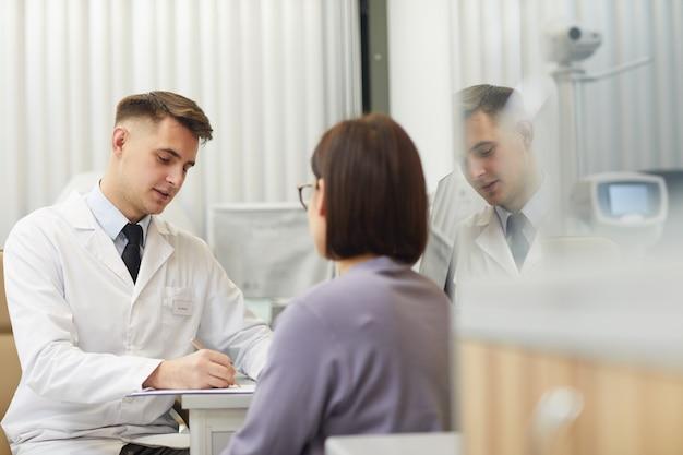 Retrato de jovem e bonito oftalmologista falando com uma paciente durante consulta na clínica