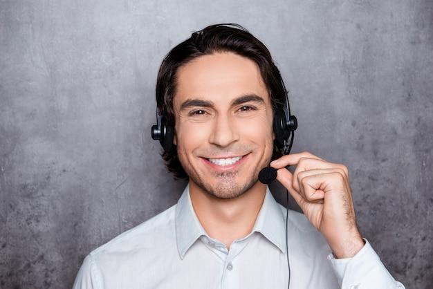 Retrato de jovem e bonito operador trabalhando em call center com fones de ouvido e sorrindo