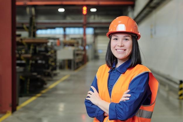Retrato de jovem e confiante engenheiro de fábrica asiático com capacete laranja e colete em pé na oficina