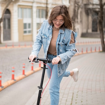 Retrato de jovem elegante andar de scooter elétrico