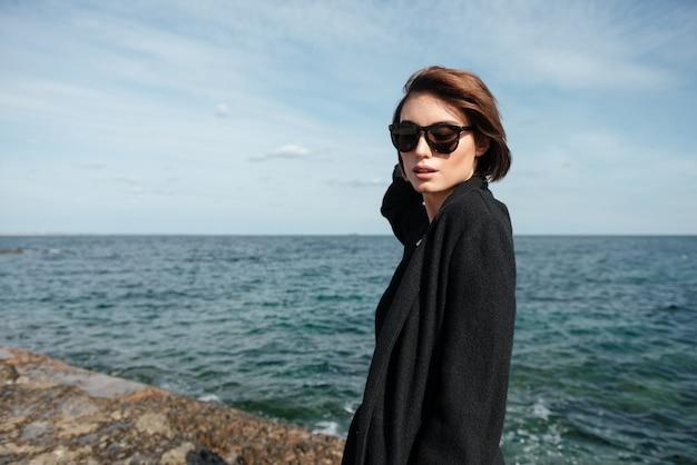 Retrato de jovem elegante com óculos escuros e casaco preto, caminhando perto do mar