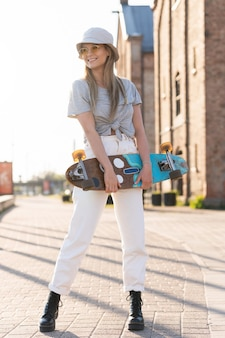 Retrato de jovem elegante com um longboard em uma cidade