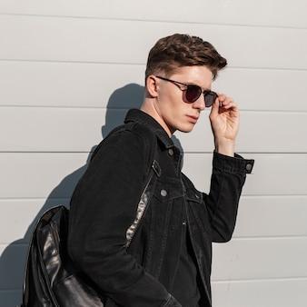 Retrato de jovem elegante em jaqueta jeans preta elegante e óculos de sol da moda