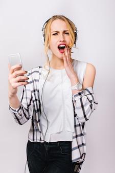 Retrato de jovem elegante emocional em roupas da moda casuais, segurando a mão perto do rosto e lendo a mensagem.