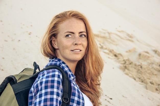 Retrato de jovem elegante hipster com cabelo ruivo e sardas em uma camisa quadriculada na encosta de duna. com mochila. viagem, caminhadas e conceito de estilo de vida ativo.