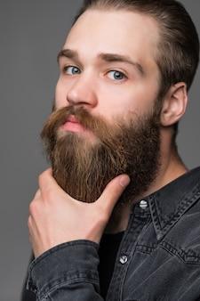 Retrato de jovem elegante pensar tocar sua barba isolada em fundo cinza