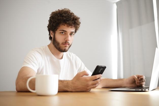Retrato de jovem elegante sério com barba por fazer, segurando o telefone celular, discando para seu amigo enquanto navega na internet em um laptop genérico, tomando uma bebida quente na mesa de madeira dentro de casa.