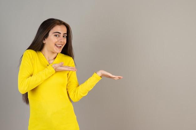 Retrato de jovem em amarelo superior em pé e posando na parede cinza.