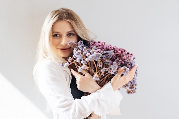 Retrato de jovem em camisa branca, segurando um grande buquê de flores secas em cinza
