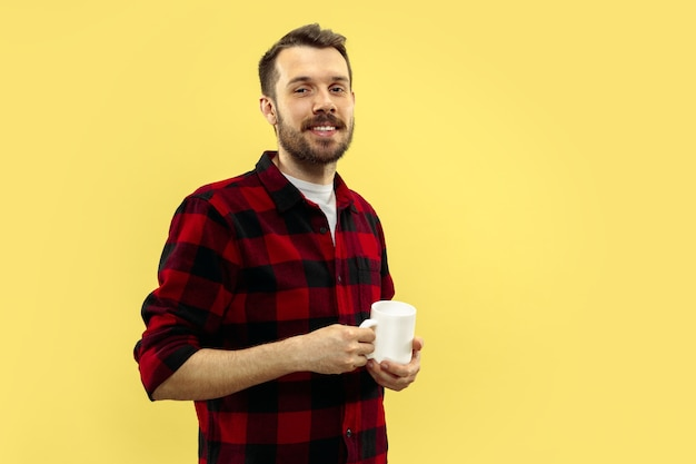 Retrato de jovem em camisa. vista frontal. cores da moda. de pé com uma xícara.