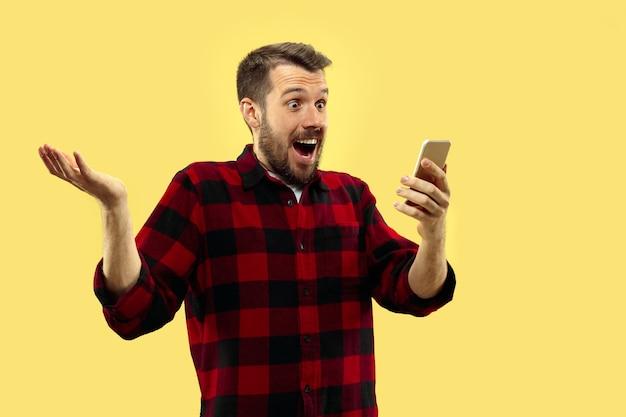 Retrato de jovem em camisa. vista frontal. cores da moda. enlouquecer de notícias no smartphone.