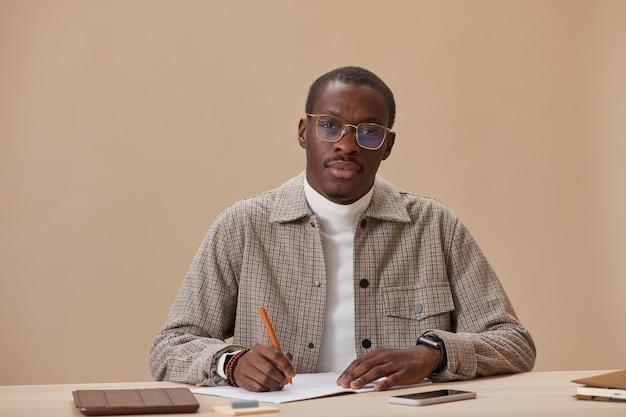 Retrato de jovem em óculos, sentado à mesa com livros e estudando