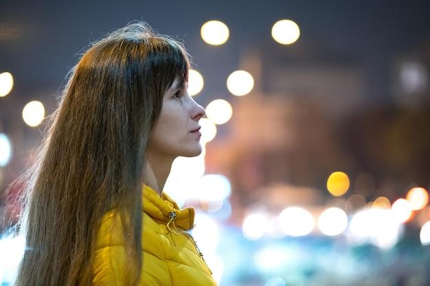 Retrato de jovem em pé ao ar livre na rua da cidade à noite.