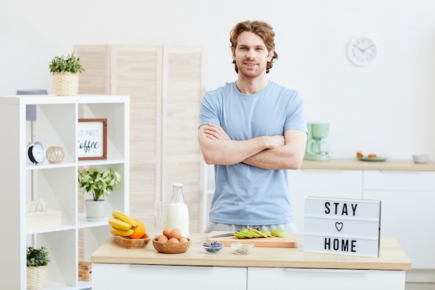 Retrato de jovem em pé com os braços cruzados e sorrindo na cozinha doméstica, ele vai preparar o café da manhã