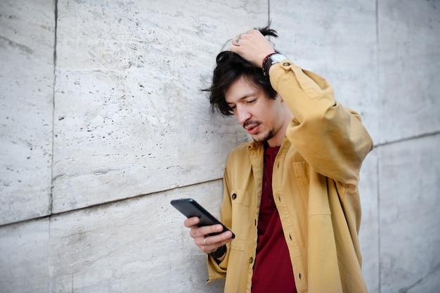 Retrato de jovem em pé contra a parede de concreto ao ar livre, usando o smartphone.