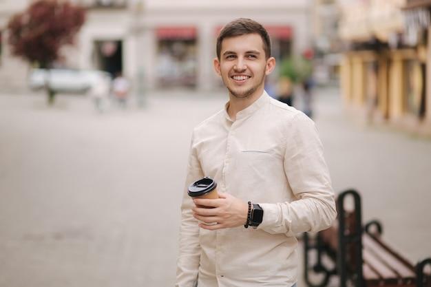 Retrato de jovem em pé na cidade com uma xícara de café