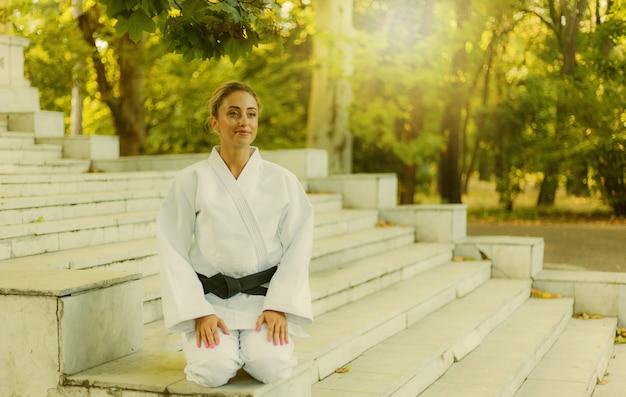 Retrato de jovem em quimono branco com faixa preta. mulher de esporte sentada na escada ao ar livre. artes marciais