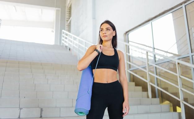 Retrato de jovem em roupas esportivas com tapete no ombro, posando ao ar livre em ambiente urbano