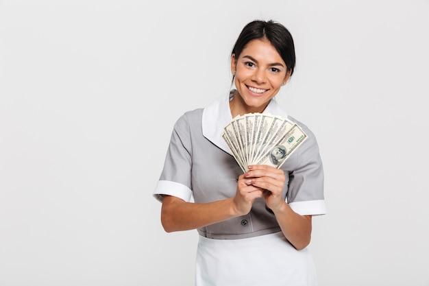 Retrato de jovem empregada feminina atraente segurando o monte de dinheiro