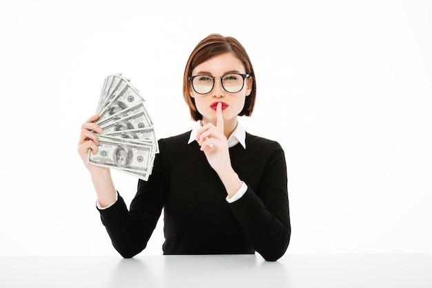 Retrato de jovem empresária com dinheiro e fazendo o gesto de silêncio