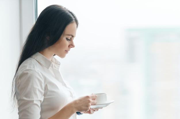 Retrato de jovem empresária em camisa branca com copo