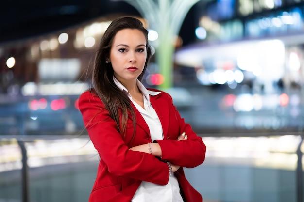 Retrato de jovem empresária em um cenário moderno de cidade à noite