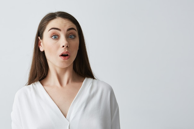 Retrato de jovem empresária linda surpresa com a boca aberta.