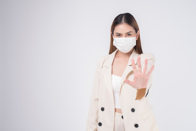 Retrato de jovem empresária usando máscara cirúrgica sobre fundo branco.