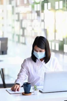 Retrato de jovem empresária waring máscara facial trabalhando com computador portátil no escritório. social e empresarial distanciando um novo estilo de vida normal.