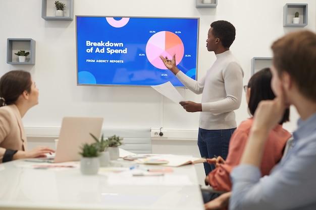 Retrato de jovem empresário africano apontando para gráfico de dados de marketing