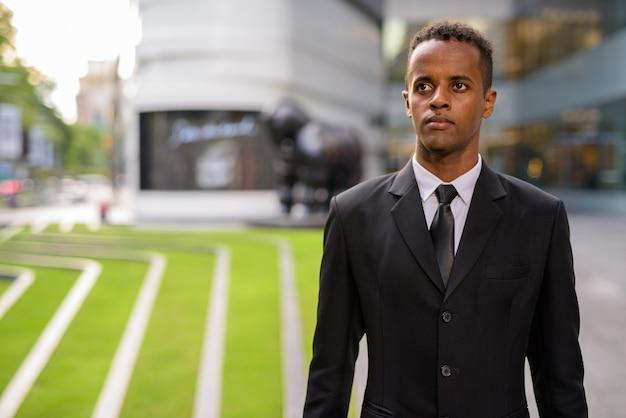 Retrato de jovem empresário africano bem-sucedido pensando ao ar livre