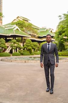Retrato de jovem empresário africano bonito caminhando ao ar livre