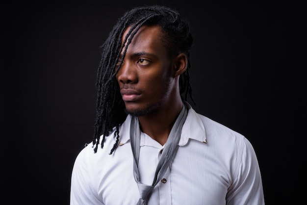 Retrato de jovem empresário africano bonito com dreadlocks no preto