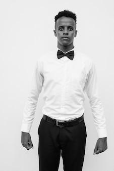 Retrato de jovem empresário africano bonito com gravata borboleta contra uma parede branca em preto e branco