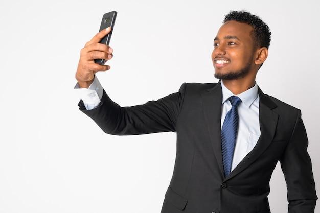 Retrato de jovem empresário africano bonito em terno contra uma parede branca